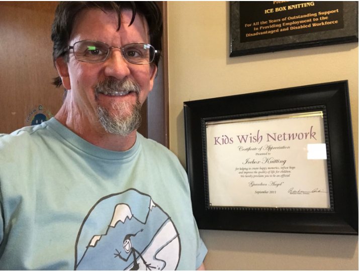 Scott Baker pictured at the company's headquarters in Longmont, CO next to Icebox Knitting certificate of appreciation for recognition as a 2-time Guardian Angel.
